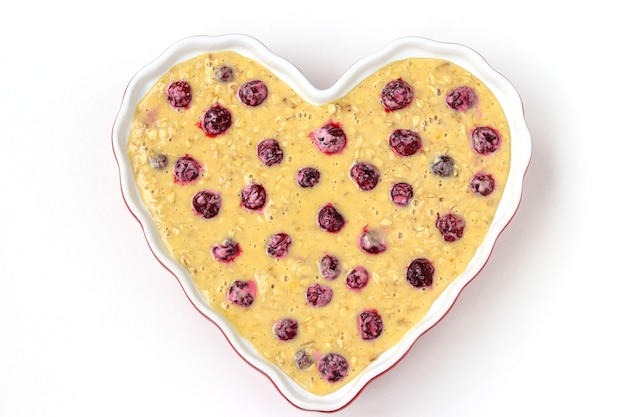 Dough for oatmeal cake with cherries in ceramic form in the shape of a heart on a white background, top view