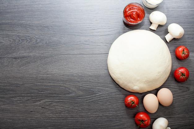 Тесто на деревянном столе, рядом с яйцами, грибами, оливковым маслом, помидорами, солью и перцем