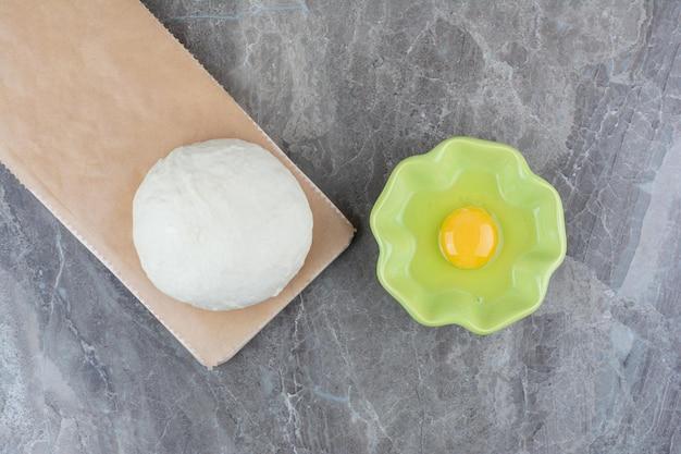 Тесто на деревянной доске с зеленой тарелкой сырого яйца. фото высокого качества