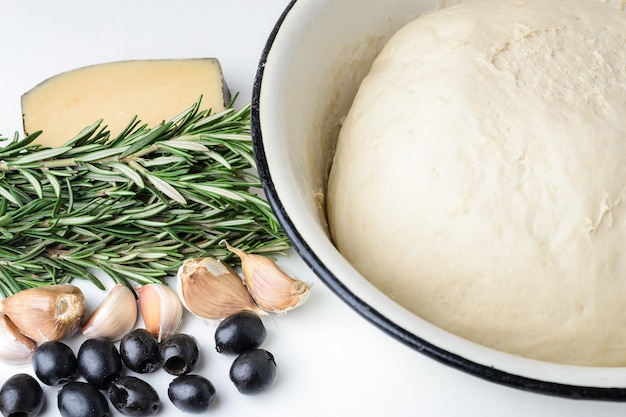 Dough for pizza in a bowl, rosemary, olives and cheese on a white background