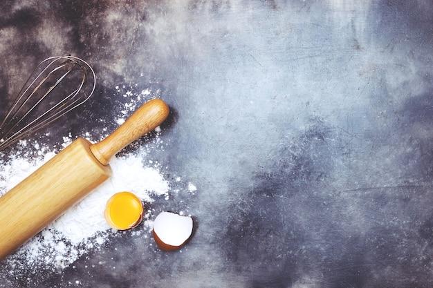 반죽 준비 레시피 빵. 제빵 재료 베이커리 요리. 달걀 노른자, 달걀 털, 롤링 핀 및 블랙 보드에 밀가루. 상위 뷰, 복사 공간.