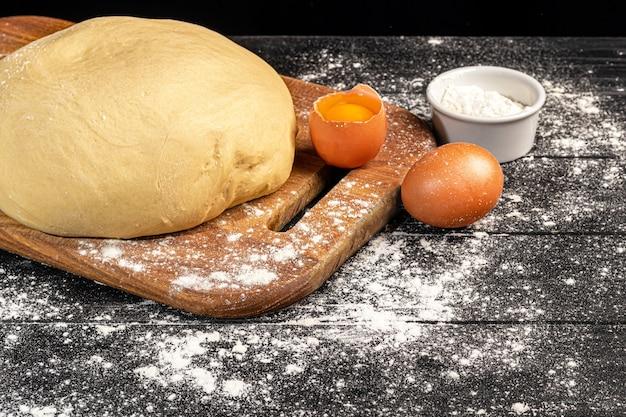 生地の準備。パイ生地。暗い背景に小麦粉と麺棒