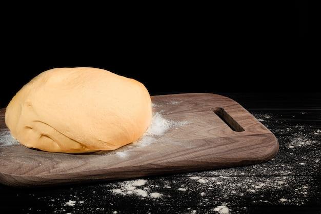 生地の準備。パイ生地。暗闇の中で小麦粉と麺棒