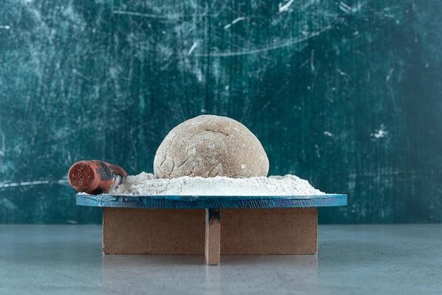 Рулет из теста с мукой на деревянной тарелке скалкой.