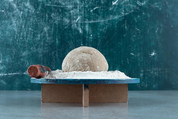 Dough roll with flour on wooden plate with rolling pin.