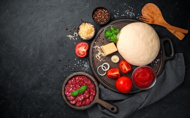 검은 배경에 향신료와 반죽, 살라미 소시지, 치즈, 토마토 소스. 복사 공간이있는 상위 뷰.