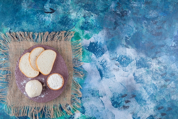 Тесто, нарезанный хлеб и миска муки на доске на салфетке из мешковины, на синем столе.
