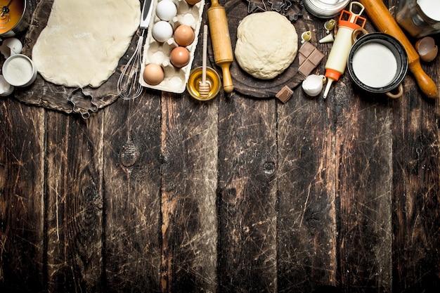 生地テーブル。木製のテーブルにさまざまな食材を使った新鮮な生地。