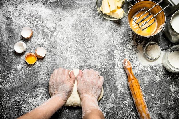 生地テーブル。女性はテーブルの上でさまざまな材料で生地をこねます。
