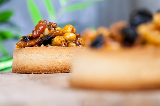キャラメルで覆われた生地のタルトナッツとドライフルーツ、さまざまな具材が入った小さな丸いタルト、ヘーゼルナッツ、ピーナッツ、その他の材料が入ったクリスピーなタルト