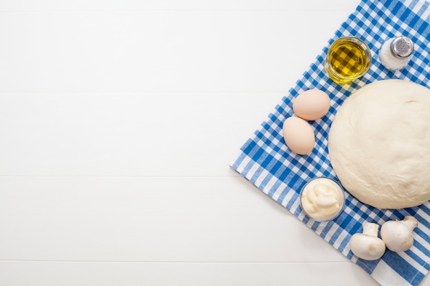 Dough on a white table, next to eggs, mushrooms, olive oil, salt and pepper, on a blue kitchen towel