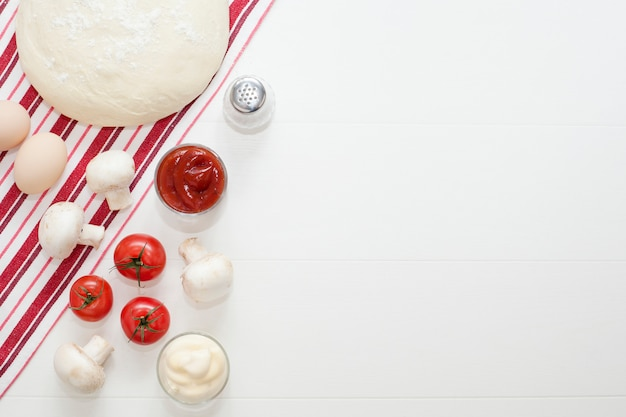 Dough on a white table, next to eggs, mushrooms, olive oil, tomatoes, salt and pepper, on a red kitchen towel.