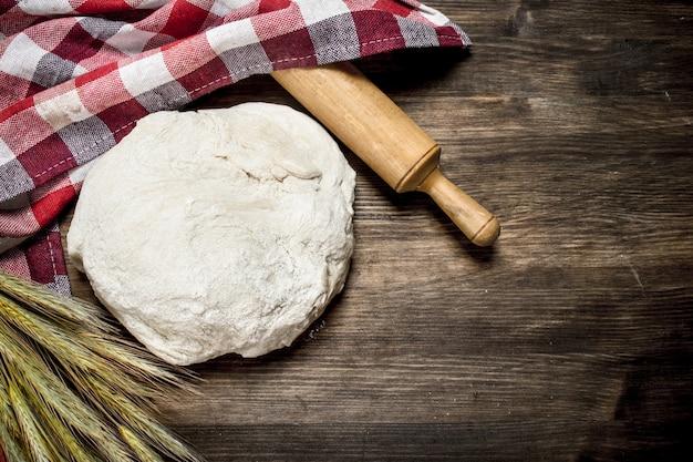 木製のテーブルに麺棒と小麦の小穂が付いた生地。