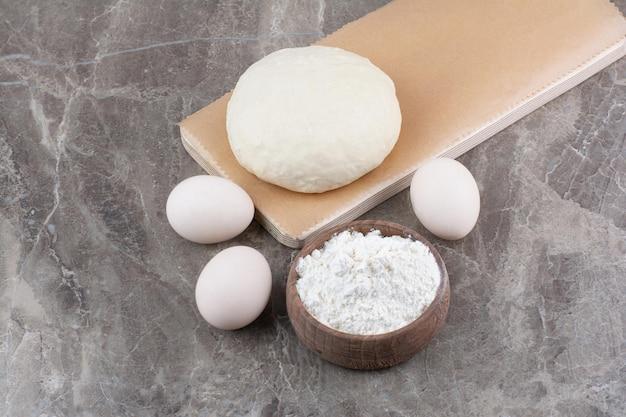 Тесто с мукой и куриными яйцами на мраморном фоне. фото высокого качества