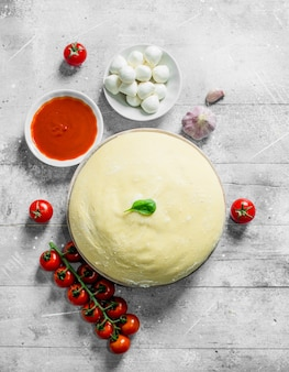 Тесто с моцареллой, томатной пастой и черри. на белом деревянном фоне