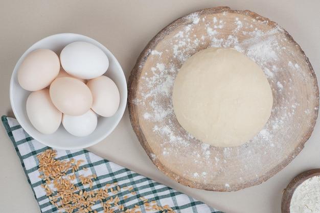 木製のまな板の上に3つの鶏の新鮮な白い卵と生地。