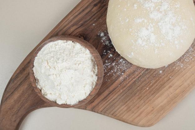 Тесто с деревянной миской муки на деревянной разделочной доске.