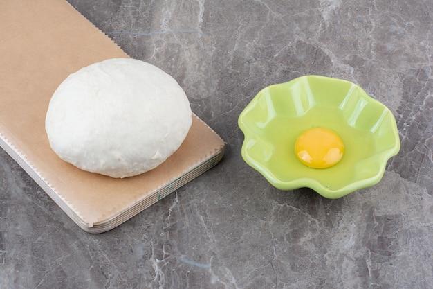 Impasto su tavola di legno con piatto verde di uovo crudo. foto di alta qualità