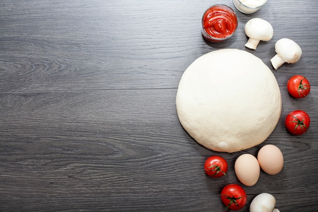 Dough on a wooden table, next to eggs, mushrooms, olive oil, tomatoes, salt and pepper