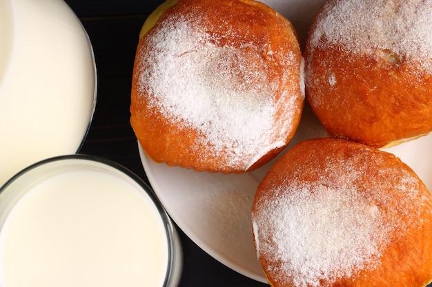 Пончик и стакан молока на темных досках