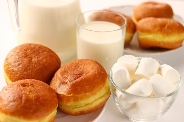 Пончик и молоко на белой поверхности