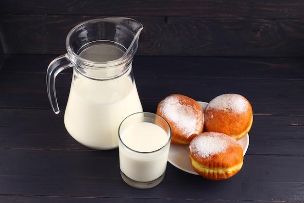 Пончик и молоко на темных досках