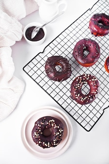 Doughnut on the baking rack glazed with chocolate cream or icing. breakfast concept.