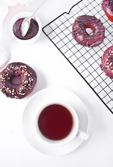 Doughnut glazed with chocolate cream or icing and cup of coffee. breakfast concept.