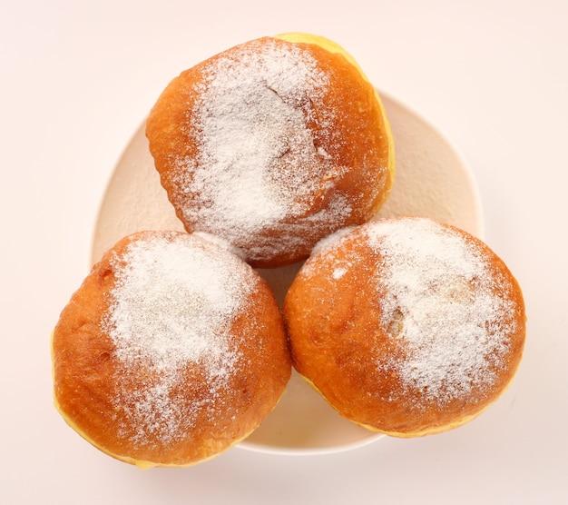 Пончик в тарелке на белой поверхности