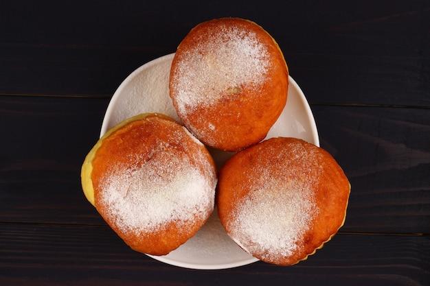 Пончик в тарелке на темных досках крупным планом
