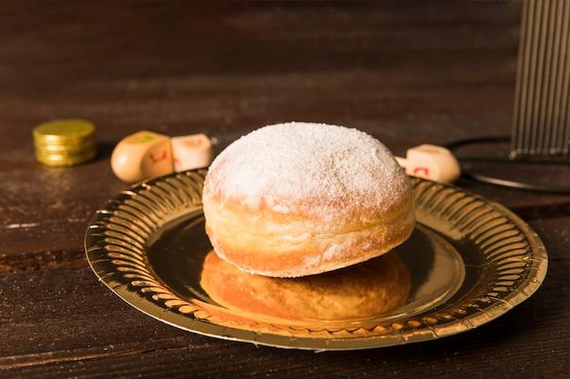 Doughnut lying near hanukkah symbols