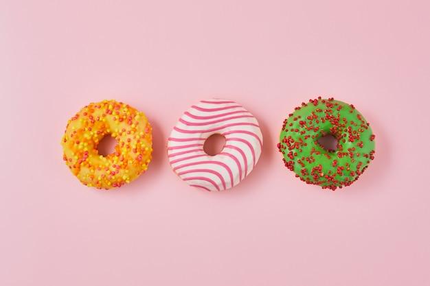 トレンディなピンクの背景に色とりどりの釉薬をかけたドーナツ。ドーナツは伝統的な甘いペストリーです。甘いドーナツ。