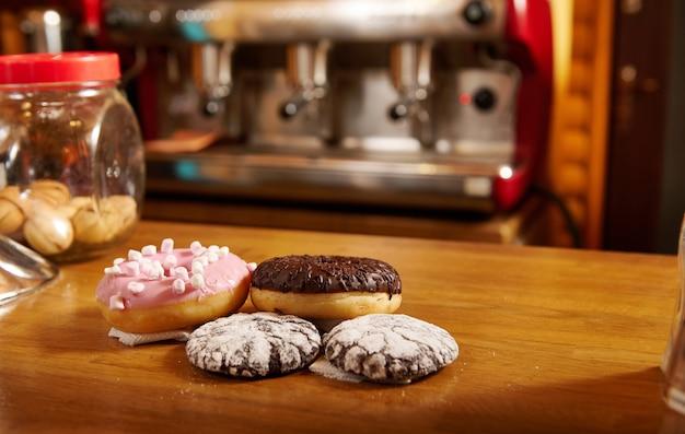 Пончики и пирожные на деревянной поверхности или столе на фоне кофемашины в кафе