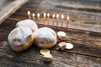 Doughnuts and Hanukkah symbols near candles