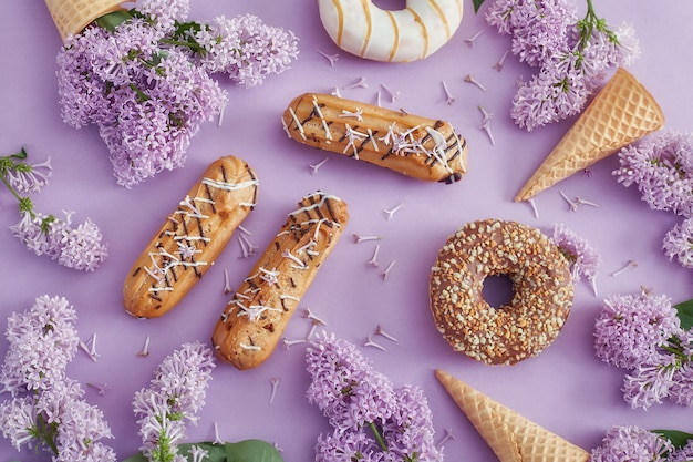 Doughnuts and cream cakes lie on the table among lilac flowers on purple paper