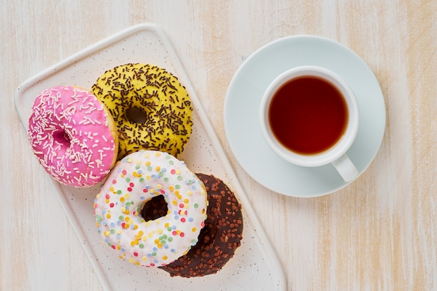 Doughnuts and tea. bright, colorful junk food. light beige wooden background. top view.