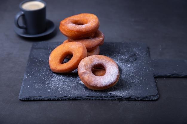 가루 설탕과 커피 한 잔을 곁들인 도넛