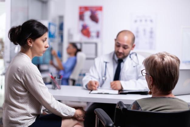 車椅子に座って相談中に医師と話している娘と障害のある母親。開業医は、病歴フォームに記入し、治療を処方する成熟した患者に質問をします