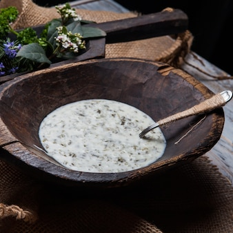 Dovga with flowers and spoon in wooden plate