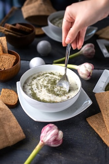 灰色の机の上に熱いテーブルスープ液体にパンローフ卵花と一緒に白いプレート内の乾燥ミントの正面図dovga皿