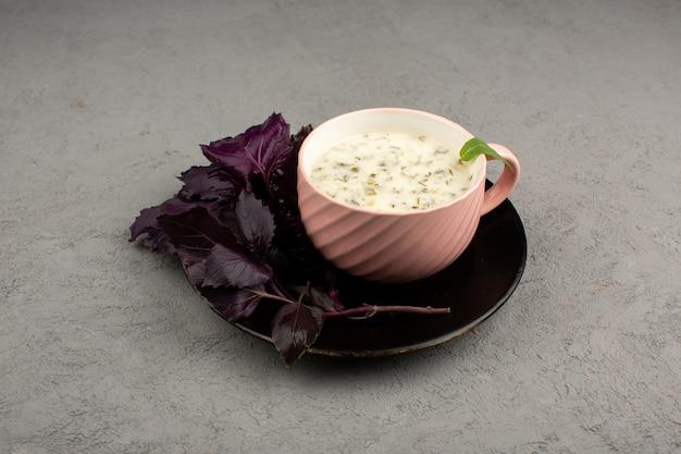 Dovga伝統的な東部の食事や飲み物、ピンクのカップの中にたくさんのハーブを添えて、グレーの黒いプレートに新鮮なハーブを添えて