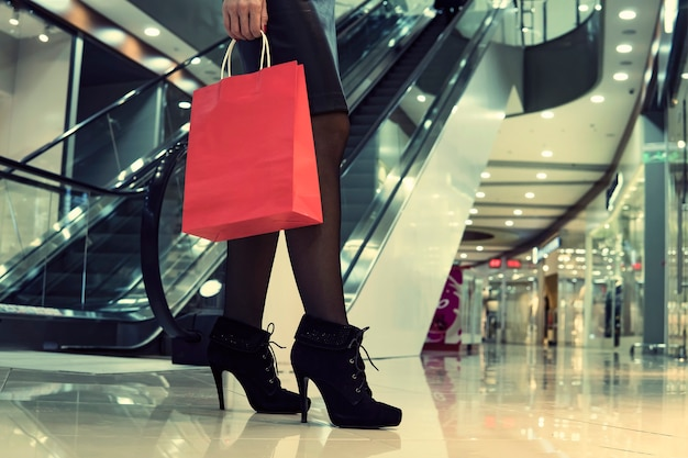 Down-top view of woman's leg wearing high-heeled anlke boots and holding red paper bag at mall's escalator background. time for shopping. female slim legs at shopping centre background. copy space.
