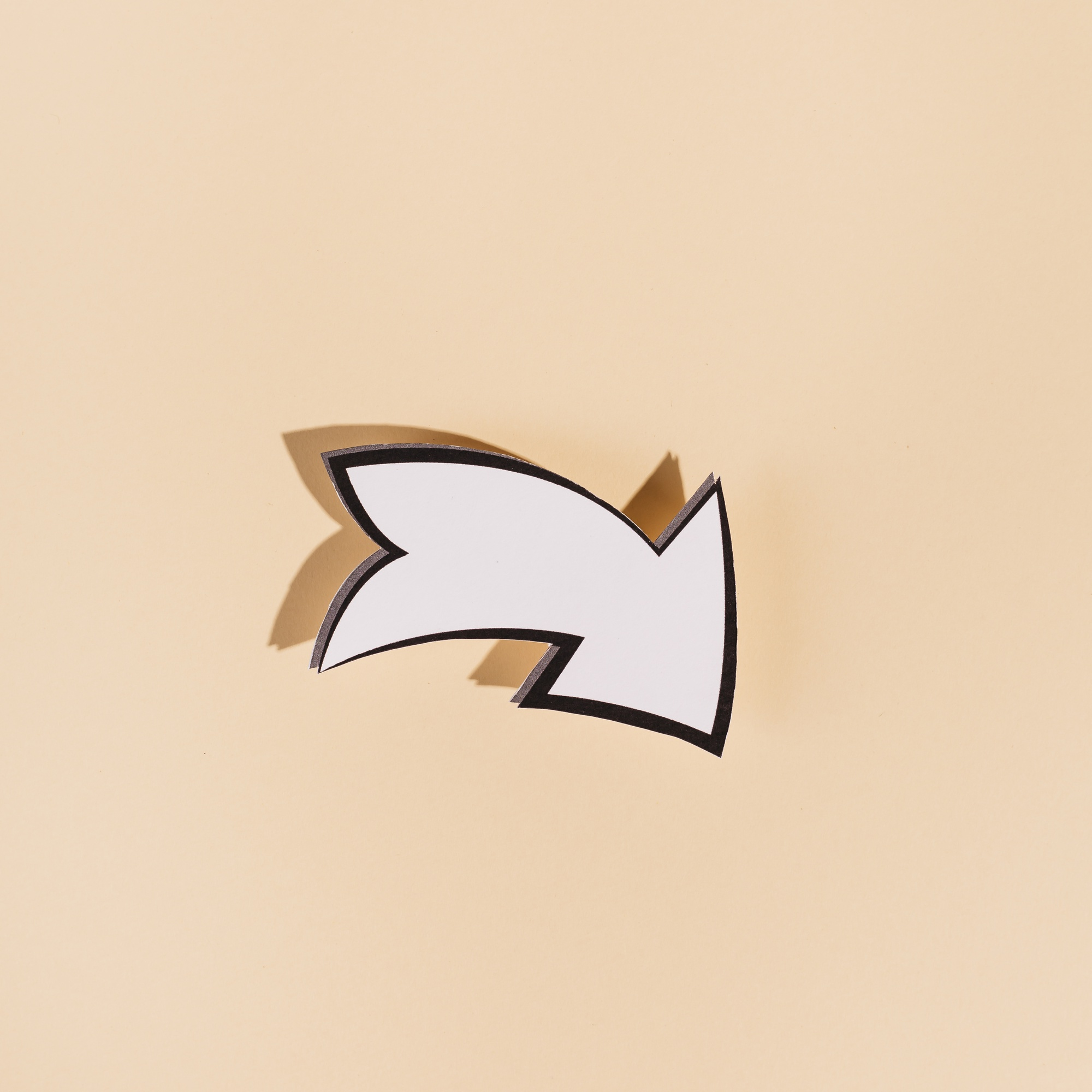 Down white directional arrow on beige background