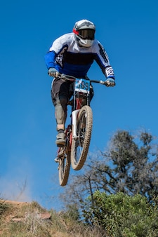 Downhill competition, biker jumps fast in the countryside.