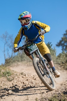 Downhill competition, biker rides fast in the countryside.