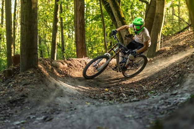 Downhill mountain biker in motion crossing trails.