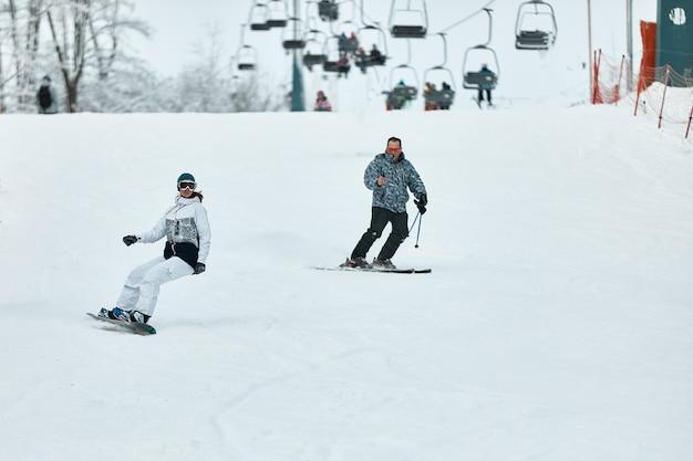 다운 힐 스키어. 스노 보더와 스키어는 산에서 눈을 타고 있습니다. 내리막 길 타기. 모험 스키어 시즌. 스키 및 스노 보드 리조트. 스키 및 스노 보드 장비. 눈 스포츠 애호가.