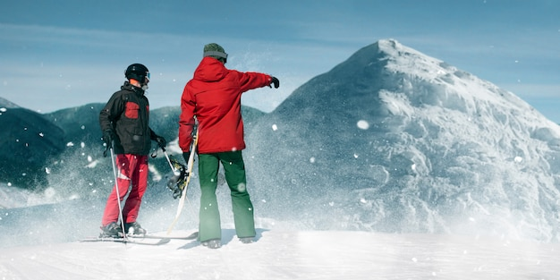 Downhill skiing, two skiers on top of the mountain, blue sky . winter active sport, extreme lifestyle
