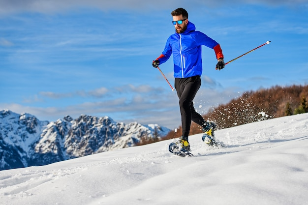Спуск на снегоступах спортсмен во время тренировки