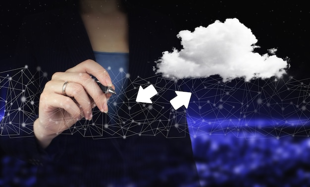 Download data storage business technology network concept. hand holding digital graphic pen and drawing digital hologram cloud, download, data sign on city dark blurred background.